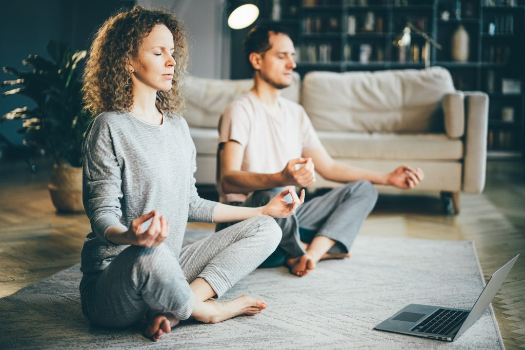 couple practising online yoga at home